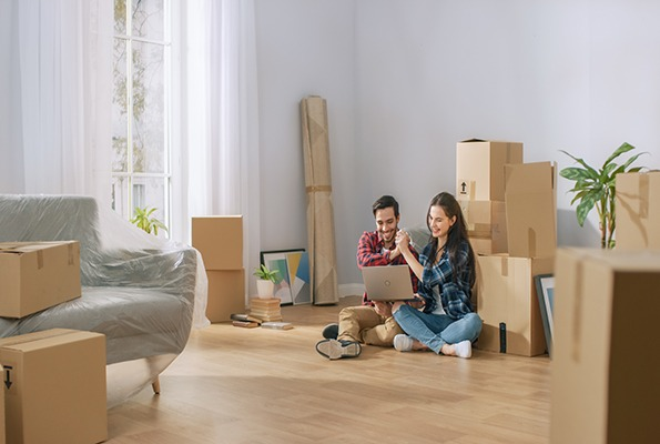 Szczęśliwa młoda para siedzi na podłodze w nowym mieszkaniu
