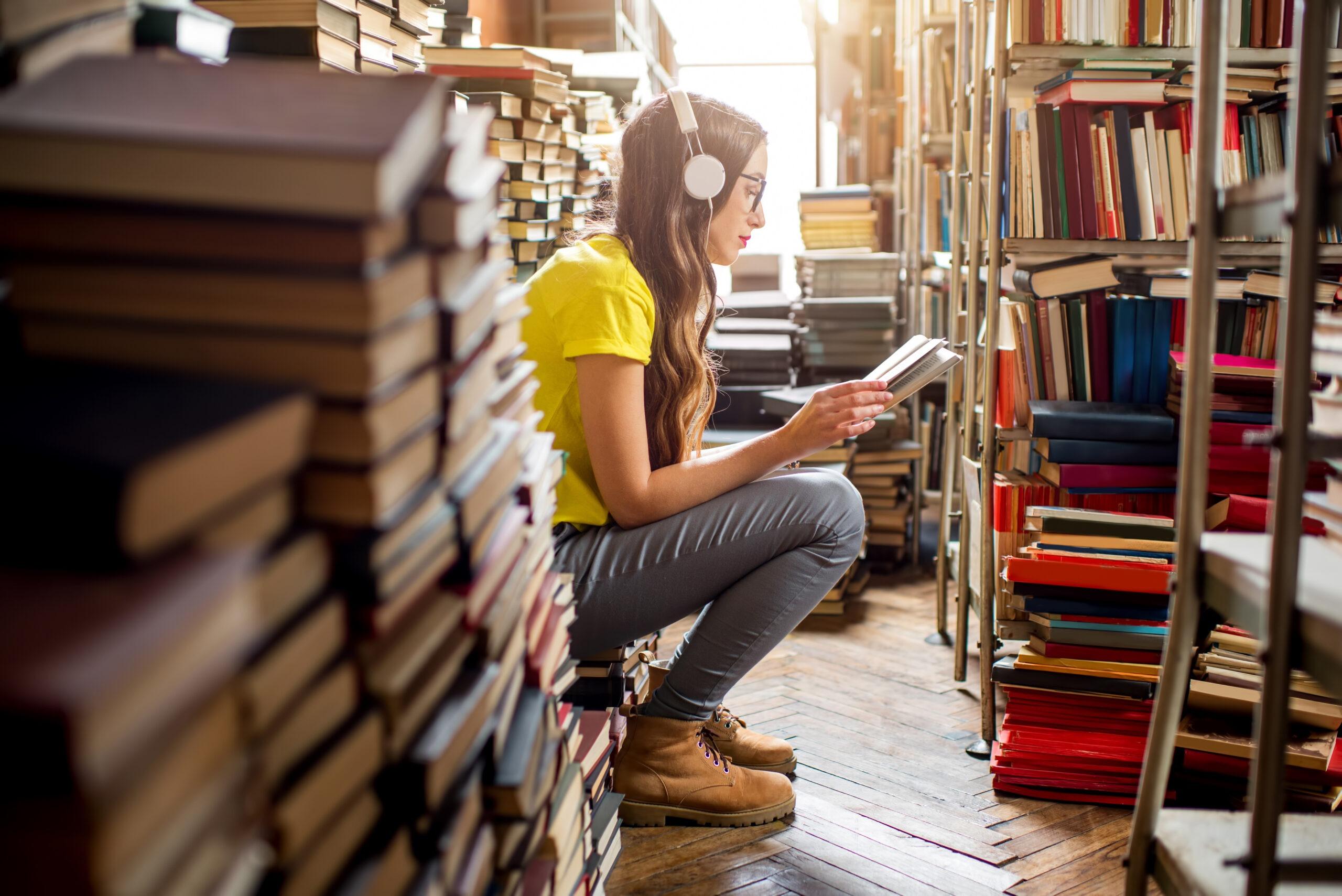 Kobieta czytająca książkę w bibliotece